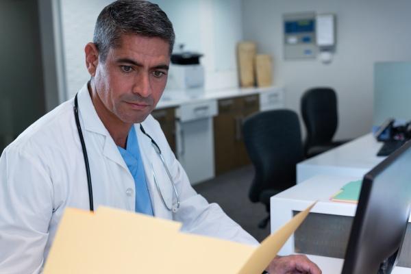 maennlicher arzt der medizinischeberichte betrachtet waehrend