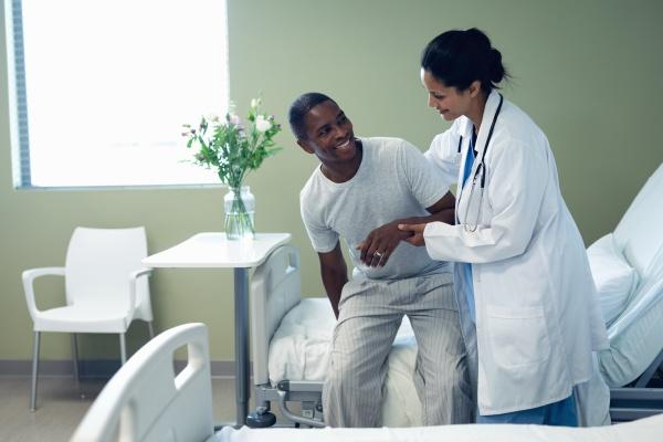 AErztin hilft maennlichen patienten auf dem