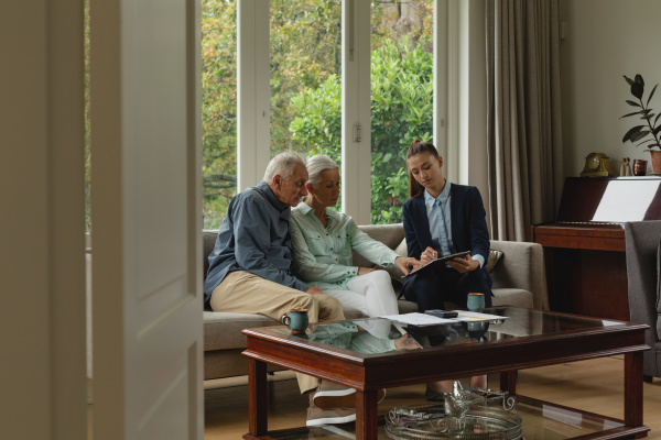 aktives seniorenpaar diskutiert mit immobilienmakler ueber