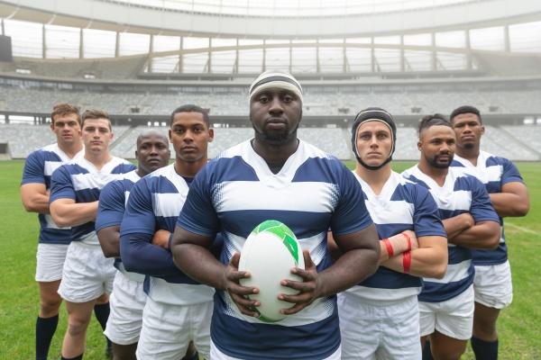 gruppe verschiedener maennlicher rugbyspieler die zusammen