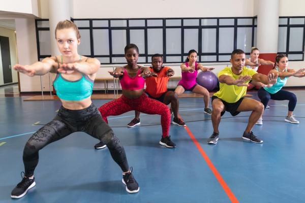 weibliche trainerin trainiert menschen yoga im
