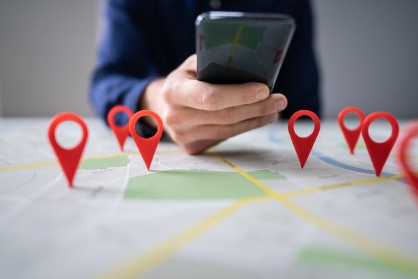 karte mit rotem standortmarker und mobiltelefon