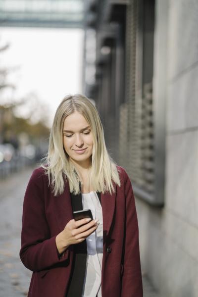 blonde geschaeftsfrau mit smartphone in der