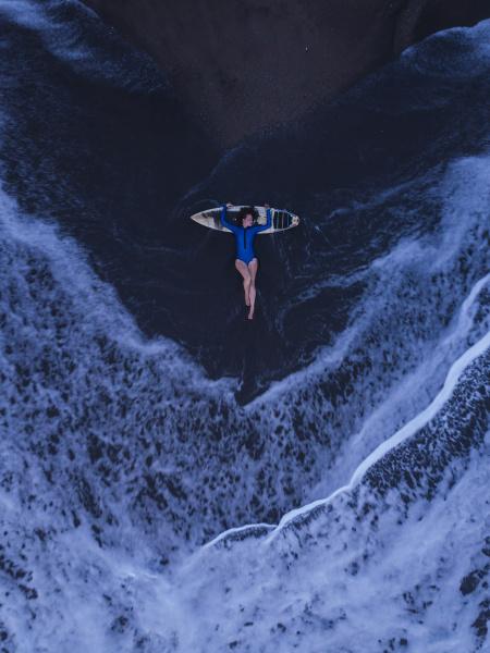 luftaufnahme junger frau mit surfbrett am