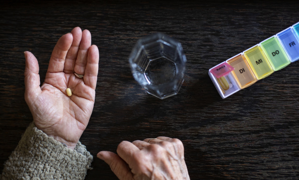 seniorin nimmt medizin wasserglas und pillen