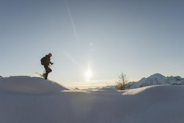 frau wandern mit schneeschuhen im neuschnee