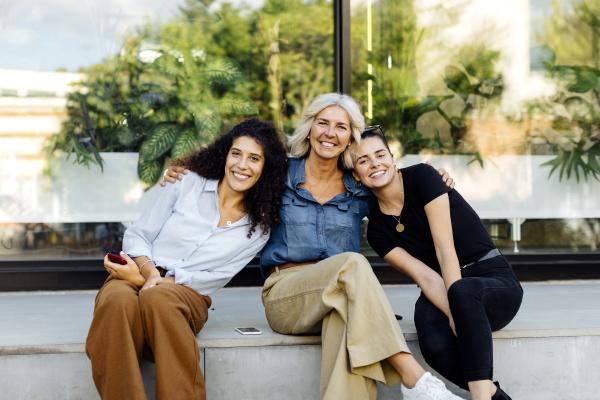 drei frauen sitzen auf der bank