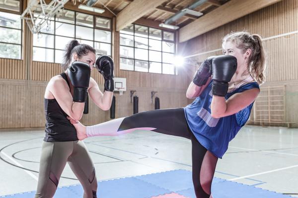 kickboxerinnen ueben in sporthalle