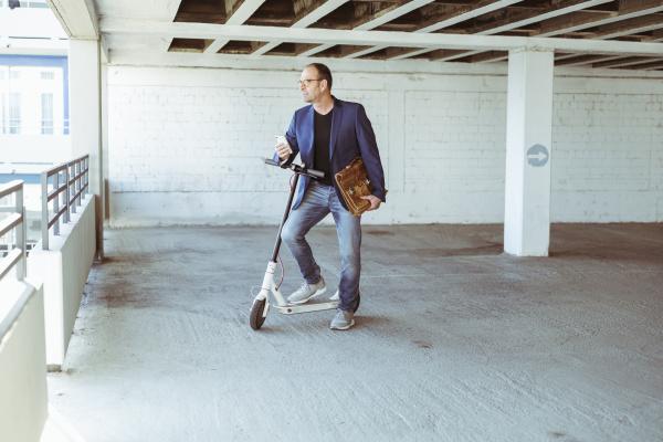 reifer geschaeftsmann mit e scooter und