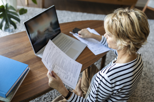 reife frau mit dokumenten mit laptop
