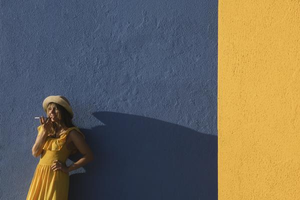 frau im gelben kleid mit smartphone