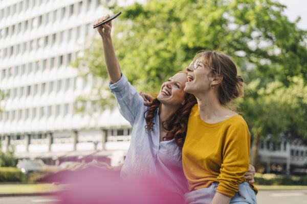 zwei glueckliche freundinnen die ein selfie