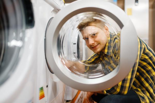 mann entscheidet sich fuer waschmaschine im