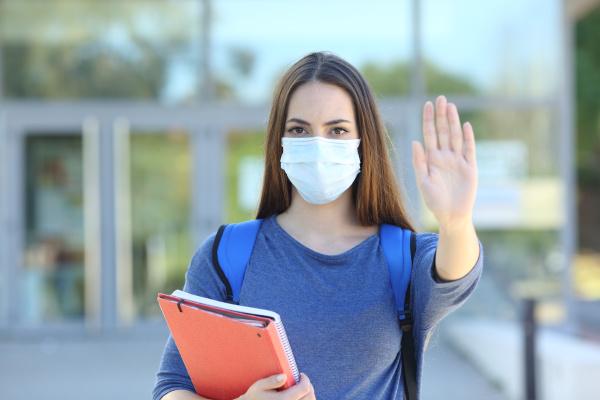 student mit einer maske gestikulieren stopp