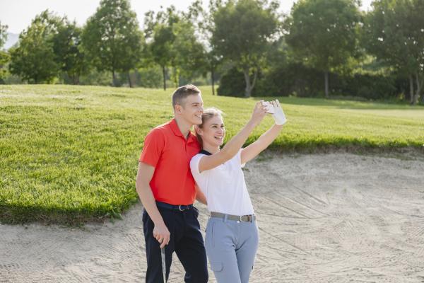 paar macht selfie auf golfplatz