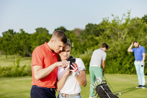 paar mit smartphone auf dem golfplatz