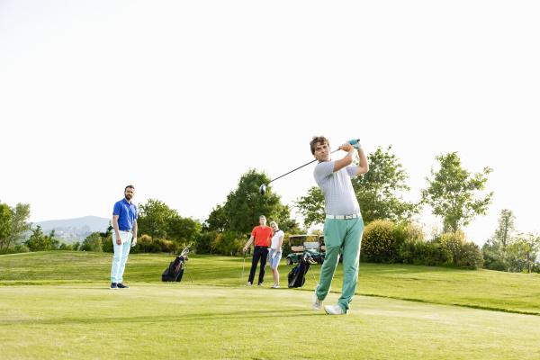 freunde die auf dem golfplatz golf