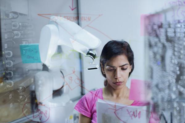 ingenieurin mit papierkramplanung programmierung roboterarm