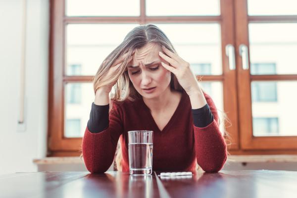 frau mit kopfschmerzen und migraene sitzt