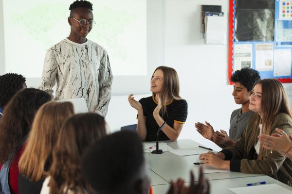 gymnasiasten klatschen fuer klassenkameraden im debattierunterricht