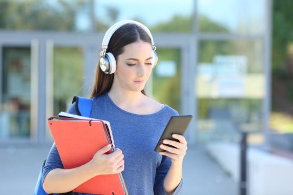 student maedchen traegt headset spielen musik