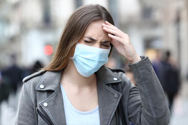 frau mit schutzmaske erleidet kopfschmerzen auf