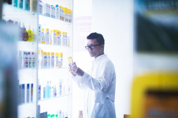 maennliche asiatische apotheker traegt brille neben
