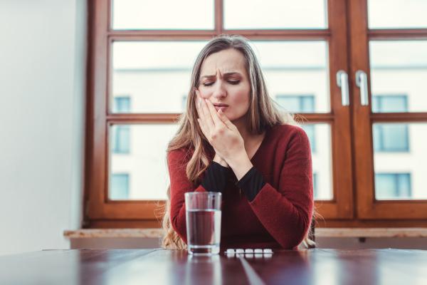 frau mit zahnschmerzen haelt ihre wange