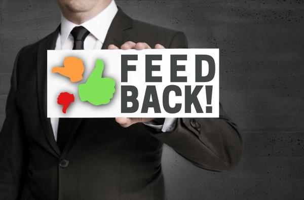 feedback zeichen wird von geschaeftsmann gehalten