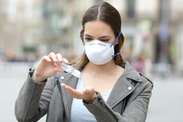 maedchen mit maske anwendung hand desinfektionsmittel