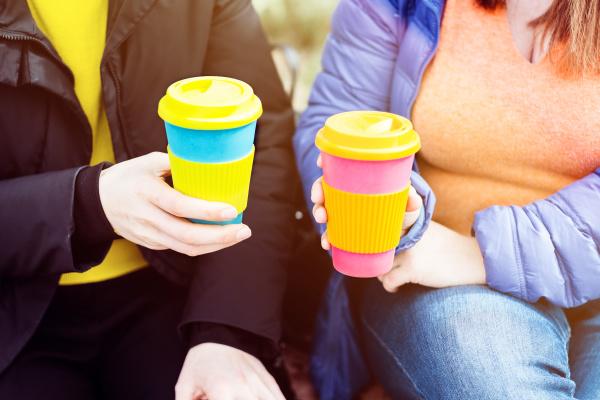 zwei frauen mit wiederverwendbaren kaffeebecher null
