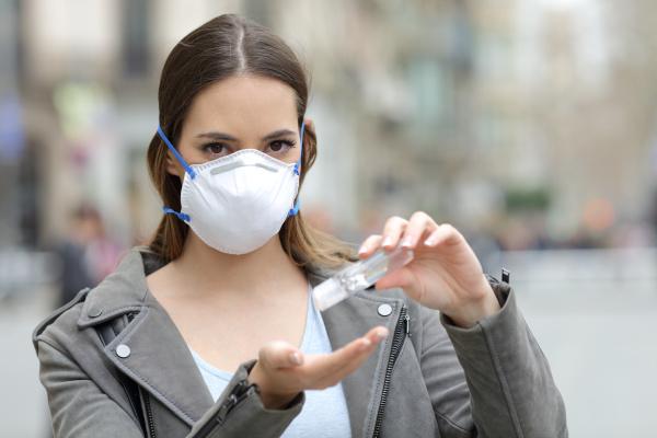frau mit schutzmaske mit handdesinfektionsmittel auf