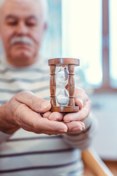 senior mann haelt sanduhr in altersheim