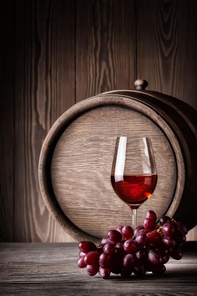 glas rotwein mit trauben