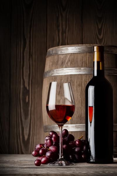glas rotwein mit flasche und fass