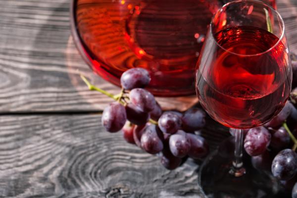 holzhintergrund mit einem glas rotwein und