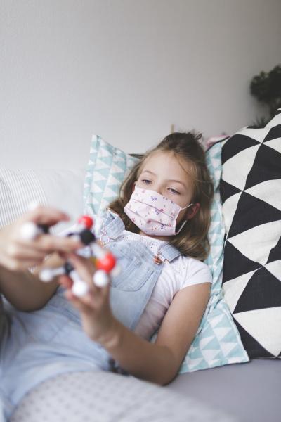junges maedchen mit schutzmaske halten molekuel