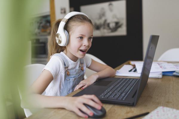 junges maedchen mit kopfhoerer und laptop