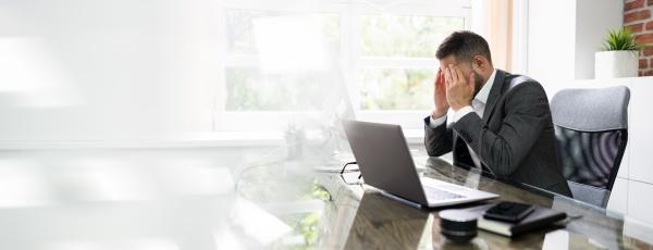 gestresster mann mit migraene und kopfschmerzen