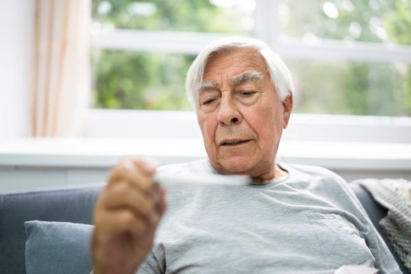 ill sick senior man check temperatur