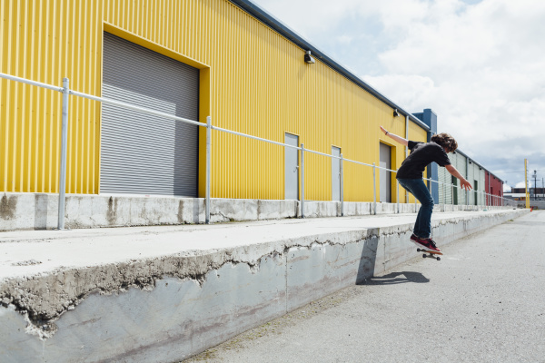 teenage boy skateboarding vor industrielager ladezone