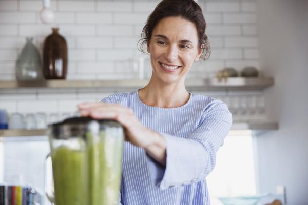 laechelnde frau macht gesunden gruenen smoothie