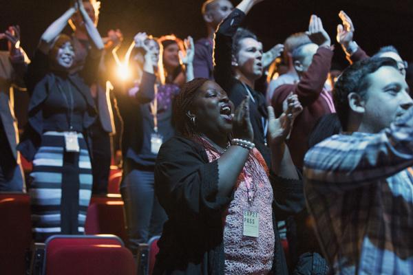publikum klatscht und jubelt im dunklen