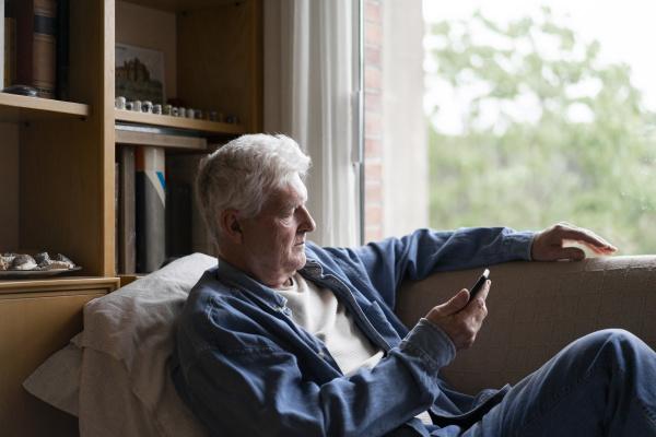 senior mann mit smartphone beim entspannen