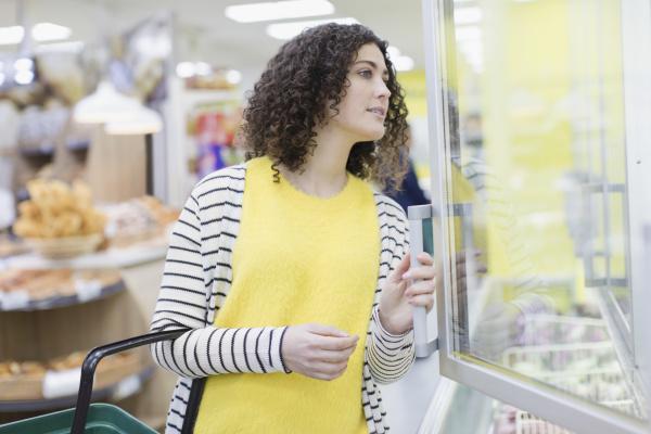 frau kauft tiefkuehlkost im supermarkt ein