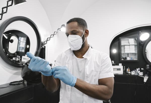 barbier traegt chirurgische maske auf wiederverwendbare