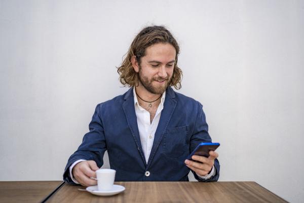 laechelnder gutaussehender geschaeftsmann mit smartphone waehrend