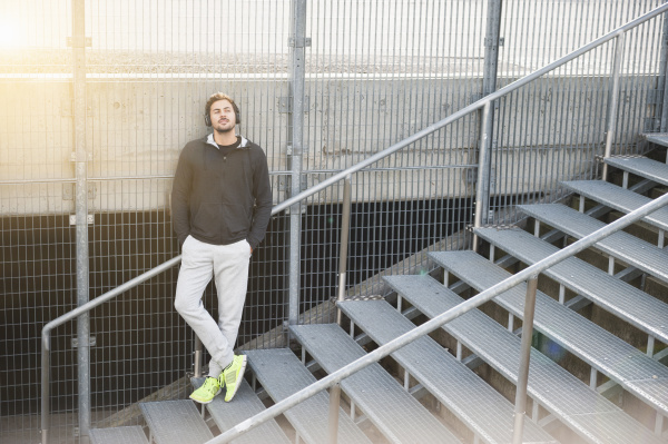 sportlicher junger mann hoert musik auf