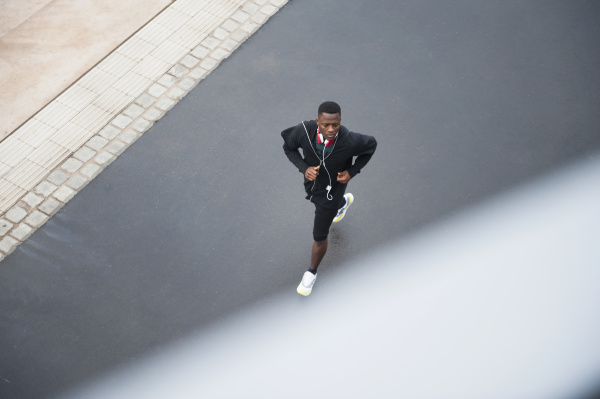 junger mann joggt mit kopfhoerer