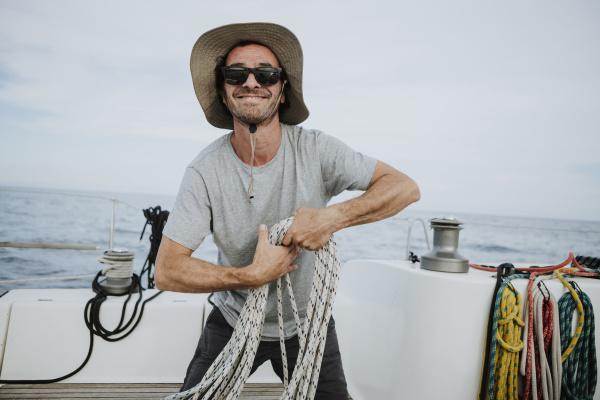 laechelnder segler mit sonnenbrille und hut